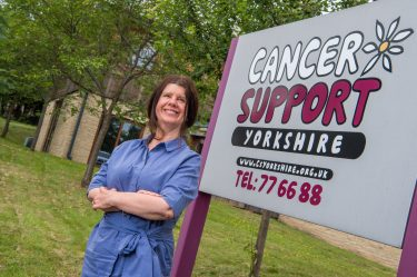 Photo of executive director Sarah next to Cancer Support Yorkshire sign