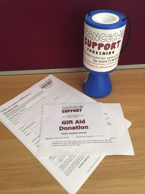 Photo of charity box and donation form